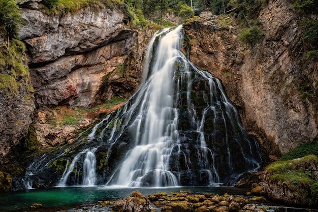 コケに覆われた岩と緑の木々の有名なゴリンジャーワッサーフォールの美しい景色 Premium写真