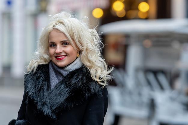 多重通りに若い笑顔金髪女性の肖像画。コピースペース。 Premium写真