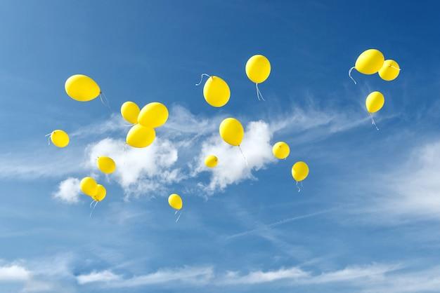 青い空に黄色の風船。 Premium写真