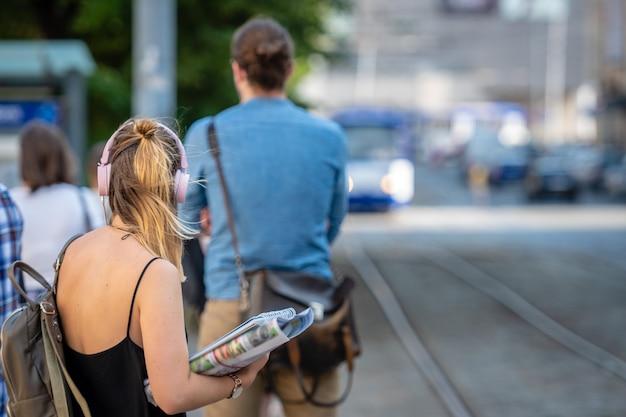 Женщина в наушниках слушает музыку и ждет трамвайной остановки. Premium Фотографии