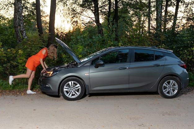 若い女性が壊れた車の前に立ってエンジンを見ますが、修理方法がわかりません Premium写真