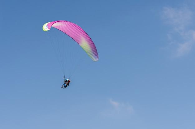 Параглайдинг в швейцарских альпах над горами против ясного голубого неба. Premium Фотографии