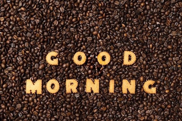 ダークコーヒー豆の背景にビスケットの文字から作られた「グッドモーニング」 Premium写真