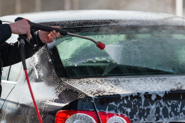 セルフサービスのタッチ洗浄のない車。水と泡で洗う。 Premium写真