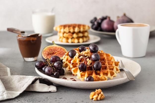 伝統的なベルギーワッフル、キャラメルソース、ブドウ、イチジク。居心地の良い秋または冬の朝食。 Premium写真