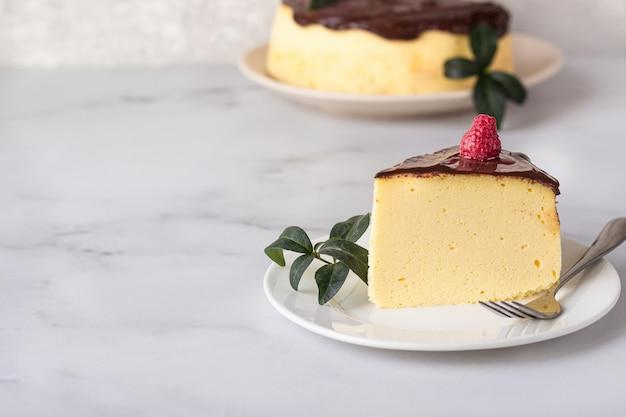 セラミックプレートにチョコレート艶出しで飾られた日本綿のスフレチーズケーキ Premium写真