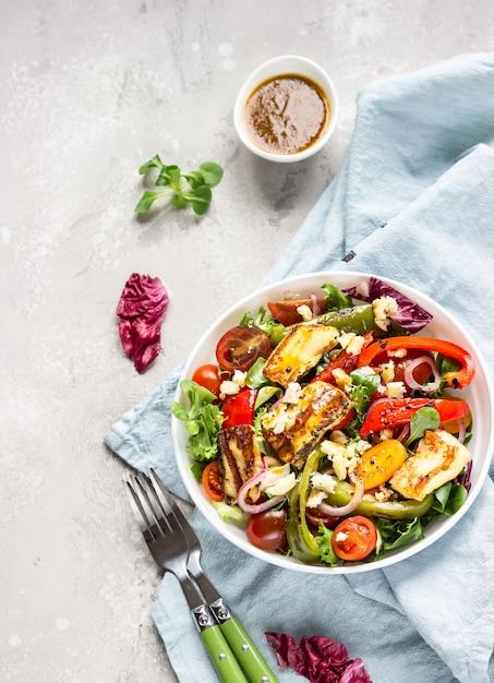 Салат из овощей с помидорами черри, запеченным перцем, миксом салата и луком с жареным сыром халуми Premium Фотографии