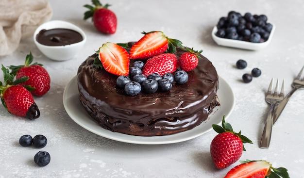 チョコレート艶出しとイチゴとブルーベリーで飾られたレーズンとチーズケーキ。 Premium写真