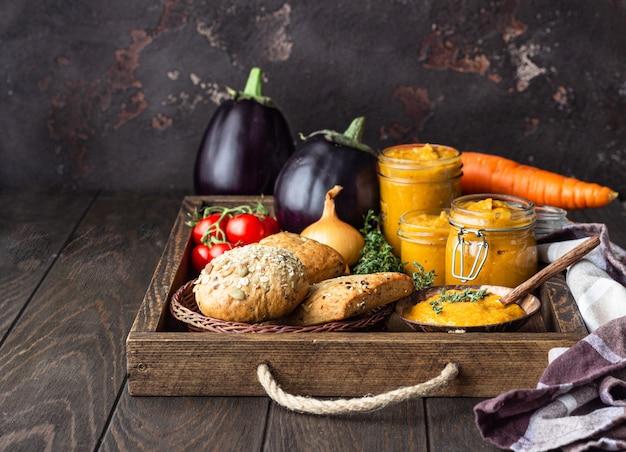 瓶、フレッシュトマト、タマネギ、ニンジン、ナス、タイムの野菜キャビアは、木製のトレイにパンを添えて。 Premium写真