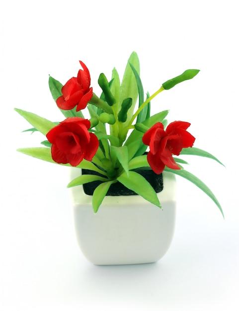Красные поддельные цветы в вазе Premium Фотографии