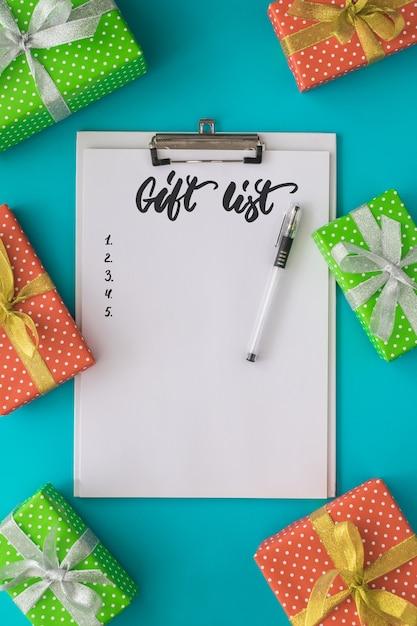 メモ帳、ペン、ギフトボックスのリストを行うクリスマスと新年の休日 Premium写真