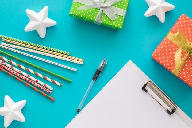 Рождество и новый год, чтобы сделать список с блокнотом, ручкой, подарочными коробками, коктейльными трубками, звездами Premium Фотографии