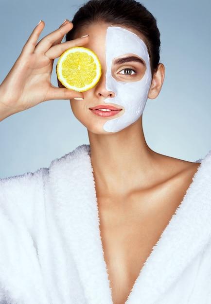 彼女の顔の前でレモンのスライスを押しながら笑顔の素敵な女の子 Premium写真