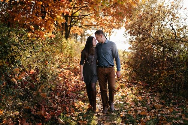 若いカップルが大好きです。秋の森公園でのラブストーリー 無料写真
