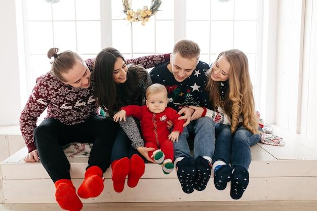クリスマスツリーの背景に贈り物とスタジオで幸せな笑顔の家族 無料写真