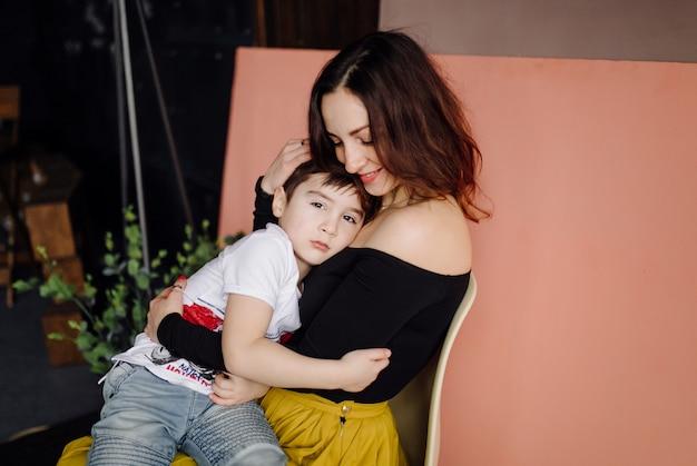 母と彼女の息子はスタジオでポーズをとって、カジュアルな服を着ています。 無料写真