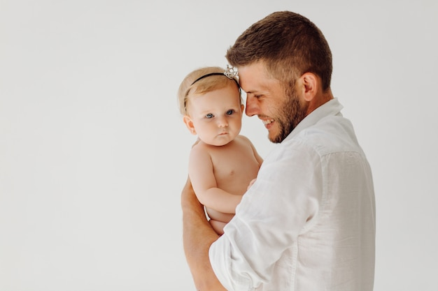 Молодой отец с красивым маленьким ребенком на руках Бесплатные Фотографии