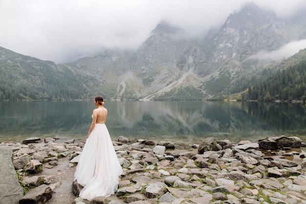 Романтическая свадьба пара в любви стоя на берегу моря глаз в польше. татры. Бесплатные Фотографии