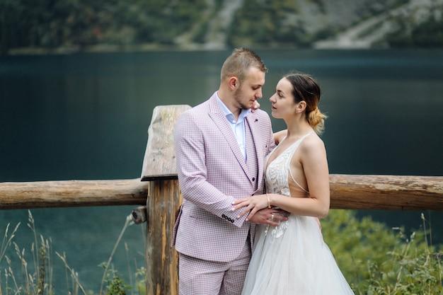 ポーランドのシーアイ湖の愛立っているロマンチックな結婚式のカップル。タトラ山脈。 無料写真