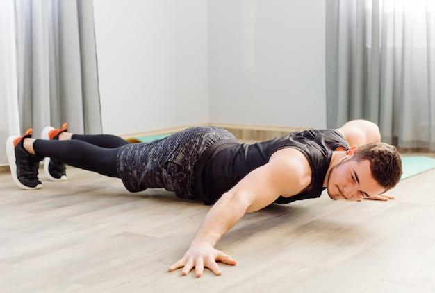 Молодой человек делает спортивные упражнения дома Бесплатные Фотографии
