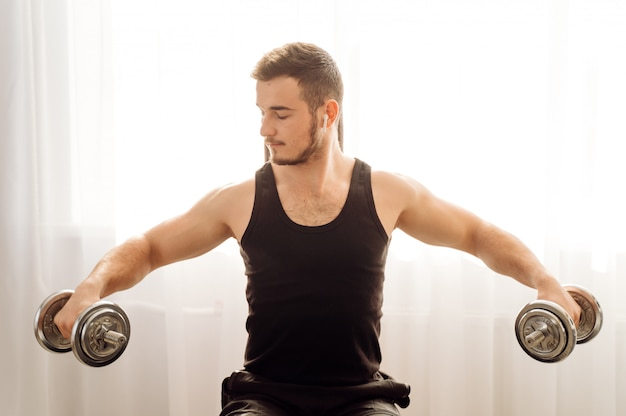 Молодой человек делает фитнес упражнения дома Бесплатные Фотографии