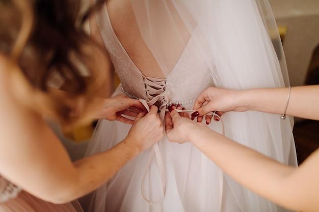 Девушки помогают невесте надеть платье Бесплатные Фотографии