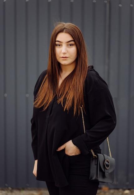 Красивая дружелюбная молодая женщина с коричневыми волосами до плеч, позирует на улице Бесплатные Фотографии
