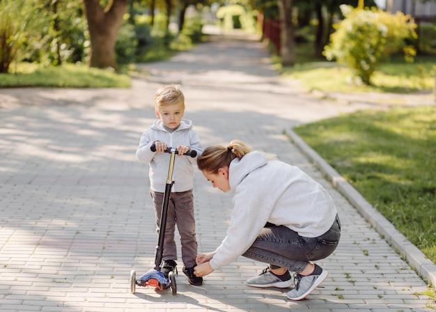 Мальчик с мамой катается в скутере по парку Бесплатные Фотографии