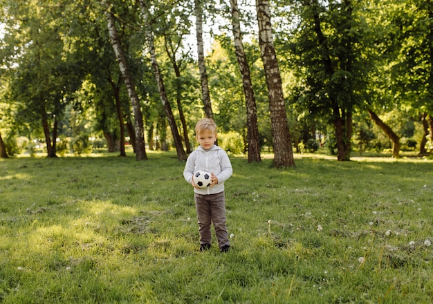 Маленький мальчик играет в футбольный мяч на открытом воздухе Бесплатные Фотографии