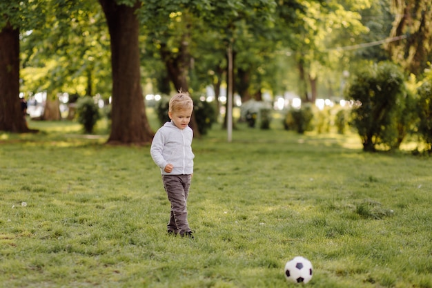 Милый маленький мальчик играть в футбол на открытом воздухе Бесплатные Фотографии