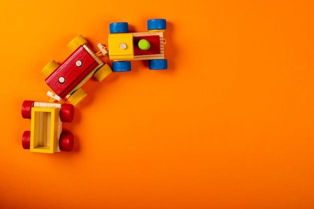 テキスト用のスペースとオレンジ色の背景に木製の電車。 Premium写真