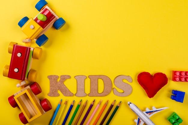 Красочный деревянный поезд на желтой предпосылке и различных покрашенных карандашах и с детьми написанными текстом и красным сердцем ткани. Premium Фотографии