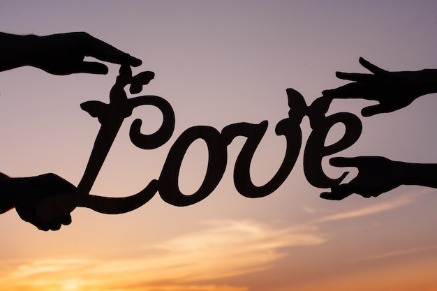 Пара держит в руках деревянную любовную надпись Premium Фотографии