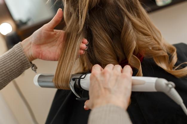 サロンヘアスタイルマスターでクライアントと働くプロの美容師は夜の髪型になります Premium写真