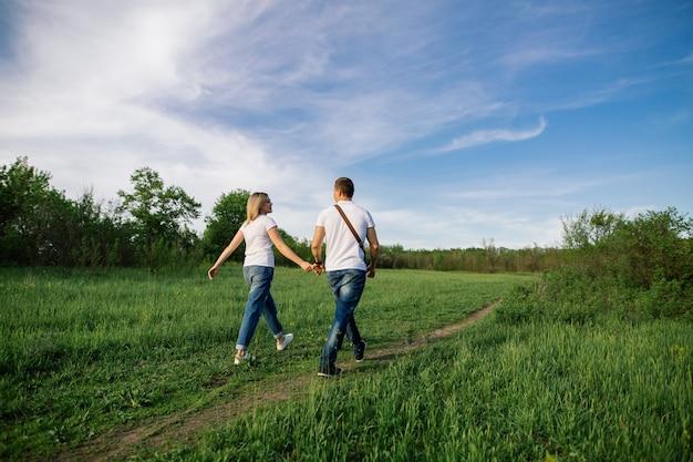 緑の野原で散歩に手を繋いでいる愛の幸せなカップル Premium写真