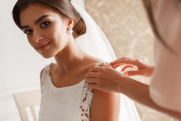 ホテルの部屋で屋内シックなドレスとベールの美しい花嫁の笑顔の肖像画 Premium写真