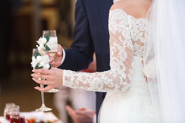 結婚式の日に装飾されたワイングラスを持つカップル Premium写真