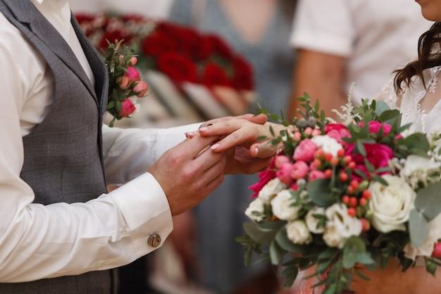 結婚式をクローズアップ。新婚夫婦は金の結婚指輪を交換します。ちょうど夫婦。彼は彼女に結婚指輪を置いた。新郎は花嫁のためのリングを置く Premium写真