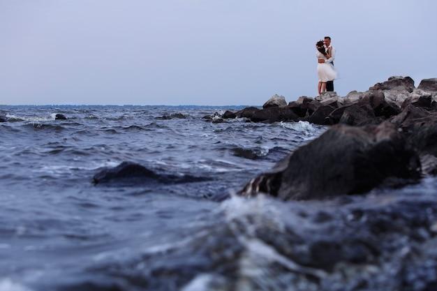 岩の多いビーチで美しい結婚式のカップル。日没で手をつないで、屋外を抱いてスニーカーでスタイリッシュな新婚夫婦。海岸に立っている新郎新婦。自然に恵まれた日。ロマンチックなデート Premium写真