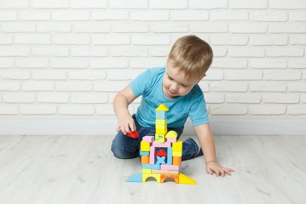 白い背景のコンストラクターで遊ぶ少年。ブロックおもちゃをしている男の子 Premium写真