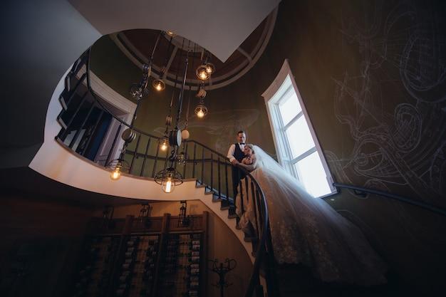 幸せな新郎新婦キスとらせん階段でハグ。美しいインテリアで愛する新婚夫婦の肖像画。結婚式の日。ちょうど夫婦の笑顔 Premium写真