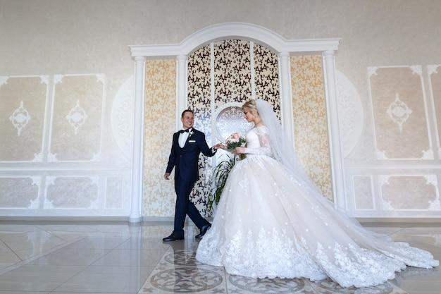 Счастливые молодожены нежно смотрят друг на друга. улыбающиеся жених и невеста, нежно обниматься в помещении в белой комнате. свадебная пара в свадебной церемонии в стильном интерьере. день пропалывания Premium Фотографии