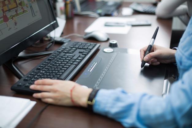 Человек учиться за компьютером крупным планом. женщина графический дизайнер, сидя на компьютере в офисе на рабочем месте крупным планом. женщина дизайнер руки работает на ноутбуке с помощью графического планшета в офисе. Premium Фотографии