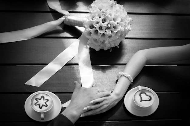 男と女の手と結婚式のブーケとテーブルの上のコーヒーカップ Premium写真