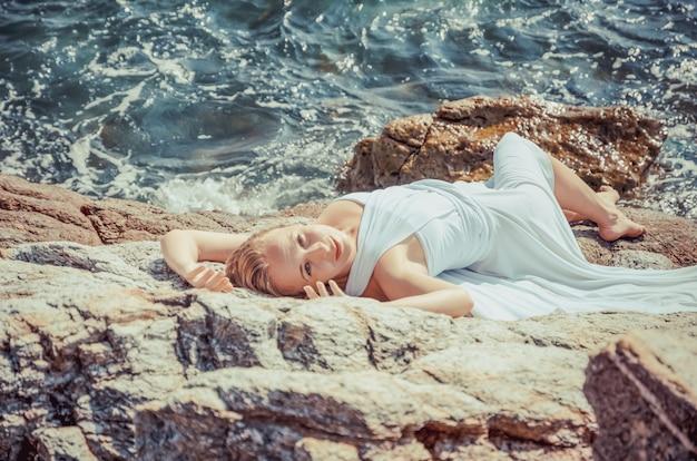 白いウェディングドレスの美しい金髪の花嫁は、海岸に立っています。熱帯の海と背景の岩。夏の休暇の概念。 Premium写真