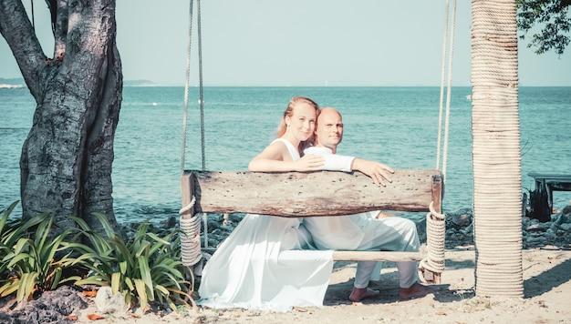 Красивая блондинка невеста в белом свадебном платье стоять на берегу моря. тропическое море и скалы на заднем плане. концепция летних каникул. Premium Фотографии