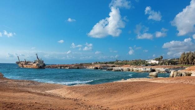 キプロス、パフォス。難破船。船は沿岸の岩に墜落した。地中海の海岸でさびた船。キプロスの観光スポット。 Premium写真
