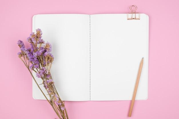 Вид сверху ноутбука и фиолетовый цветок на розовом столе Premium Фотографии