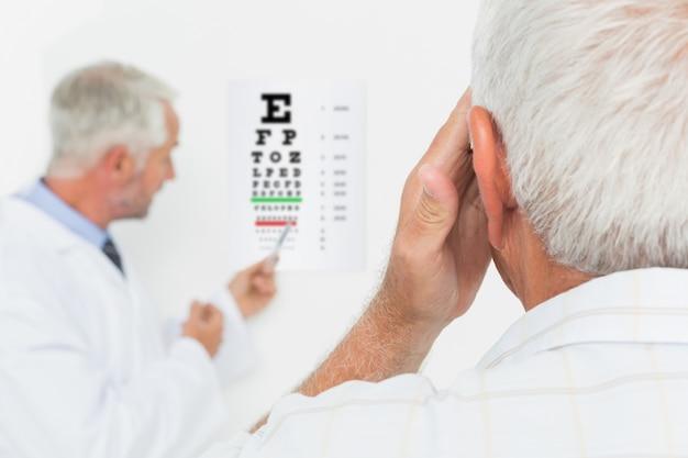 視力検査を指導している高齢者の小児科の眼科医 Premium写真