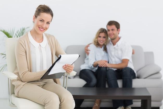 夫婦とバックグラウンドでノートを書く財務顧問 Premium写真